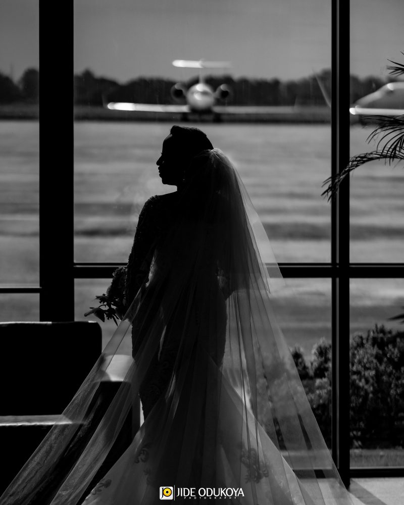 Bride in her wedding dress in front of an airplane