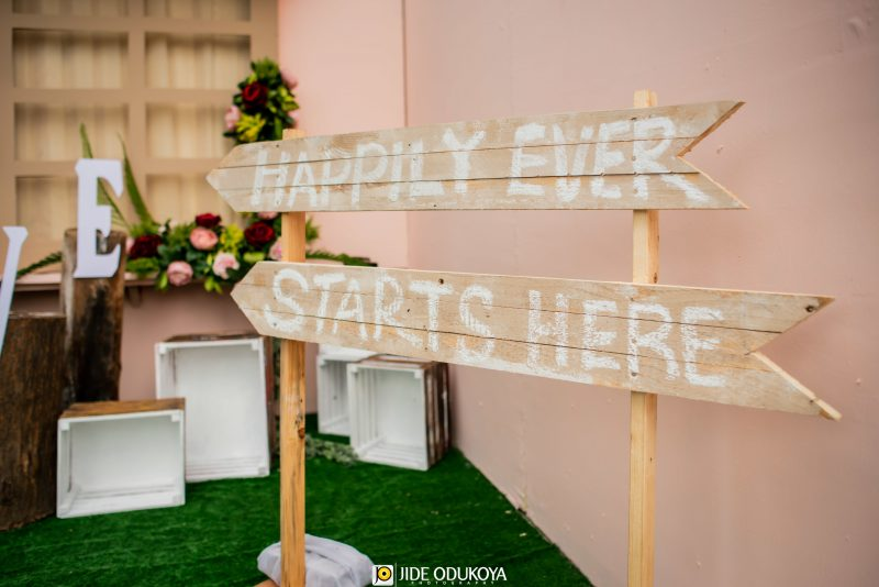 A wooden inscription with the words 'Happily Ever Starts Here'