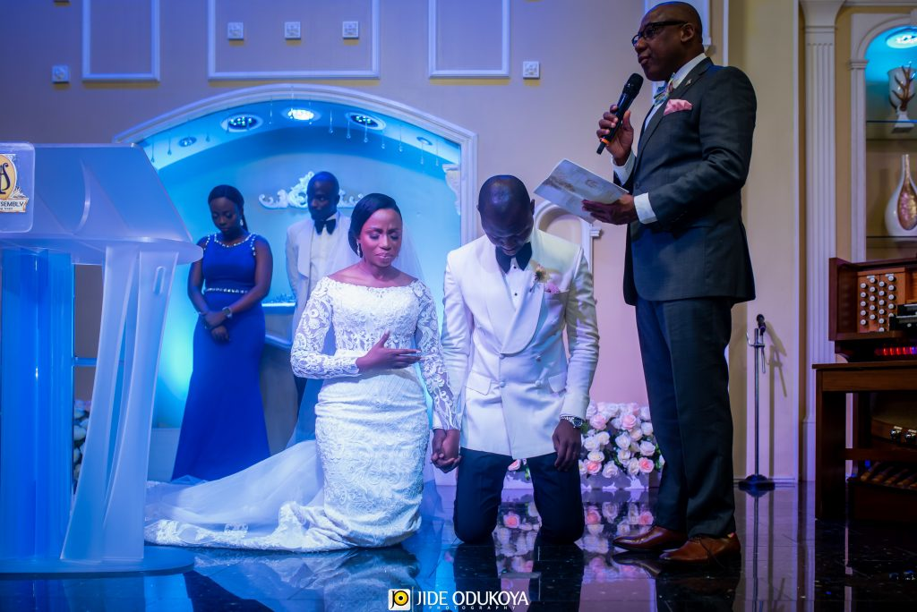 Kemi and Pelu kneeling in prayer during their church wedding ceremony