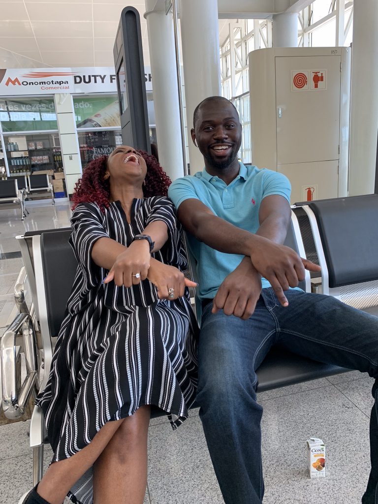 Kemi and Pelu sitting at an airport and laughing while crossing their hands (and showing off an engagement ring)